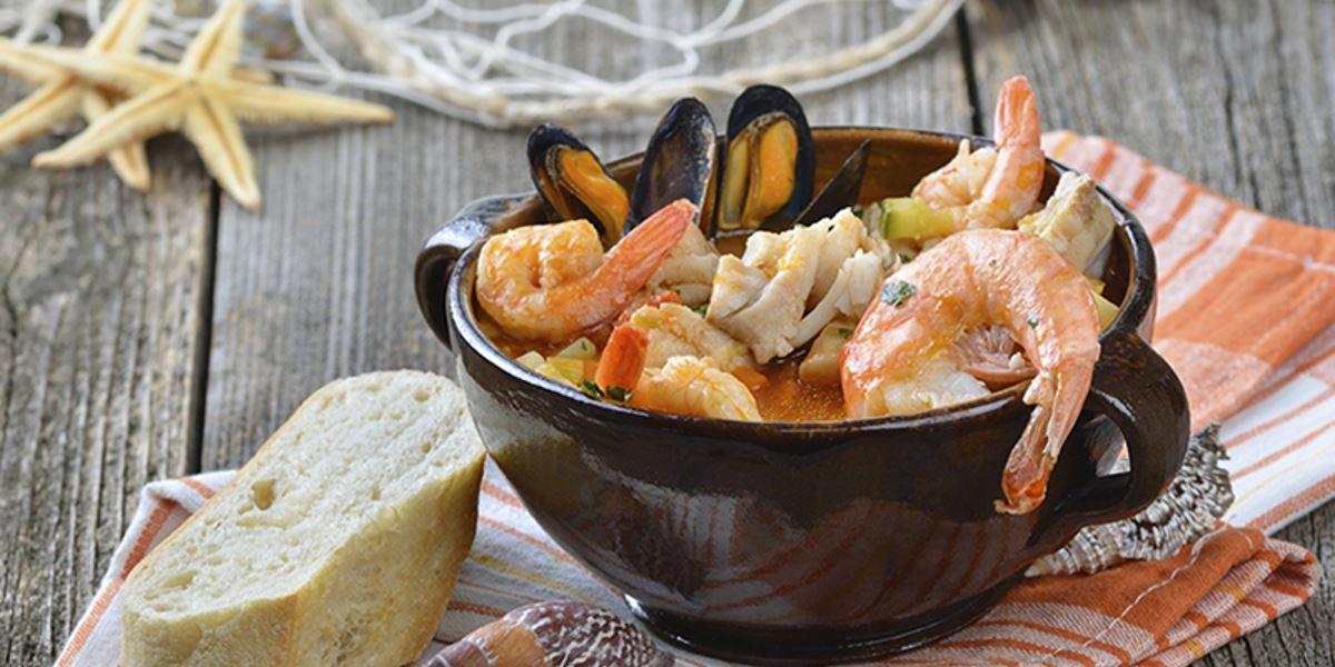 Zuppa con pesce, gamberi e cozze e pezzo di pane