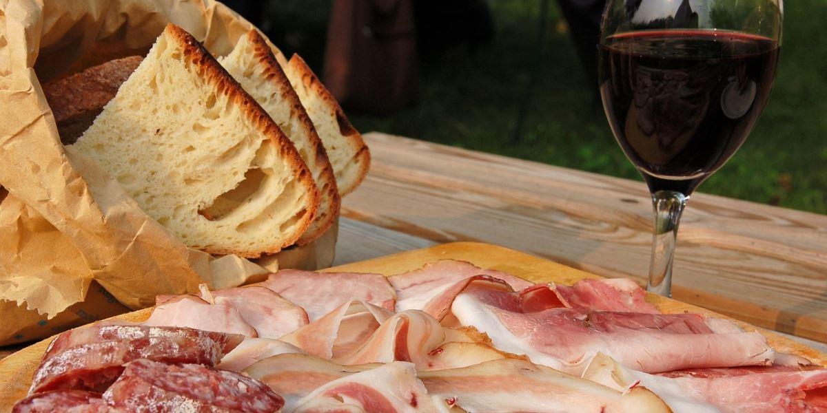 Tagliere con salame e prosciutto, pane in fette e bicchiere di vino rosso