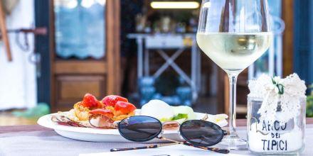 Bicchiere di vino bianco e piatto con prodotti tipici