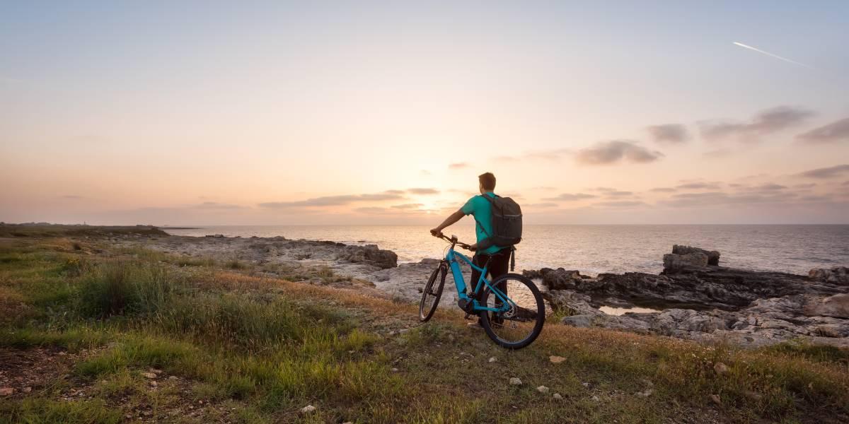 Il turismo sostenibile - Ragazzo in bicicletta che guarda il mare