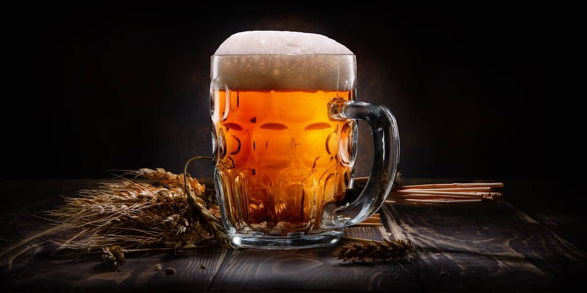 La birra artigianale in Italia - Boccale di birra e spighe di grano